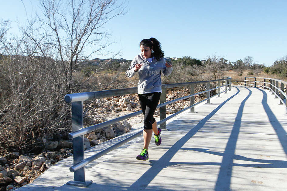 Cristal Cristia jogs across a bridge at Stone Oak Park, 20395 Stone Oak Parkway, on Tuesday, Feb. 4, 2013. The 245 acre park has 2.7 miles of trails, cave protection features, covered shelters, interpretive signage and excercise stations. Photo by Marvin Pfeiffer / EN Communities