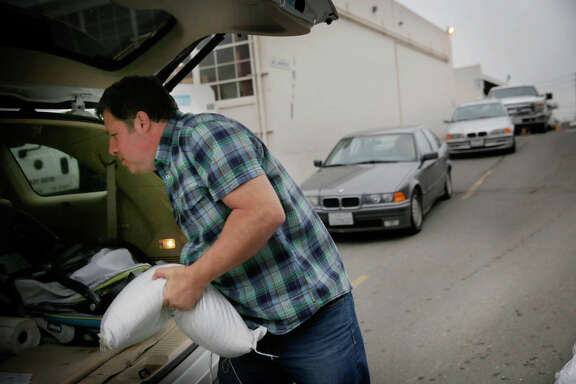 Gregory Gamp of San Francisco loads a sandbag into his car as other drivers wait in line. Gamp had to wait about two hours.