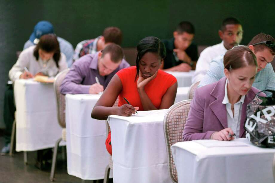 In this file photo, job seekers fill out forms before being interviewed during a job fair at Fontainebleau Miami Beach in Miami Beach, Fla. The most recent report on the U.S. job market brought the best news in years. Photo: Wilfredo Lee / Wilfredo Lee / Associated Press / AP