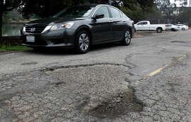 A motorist avoids potholes on Potter Street en route to the I-80 on-ramp in Berkeley.