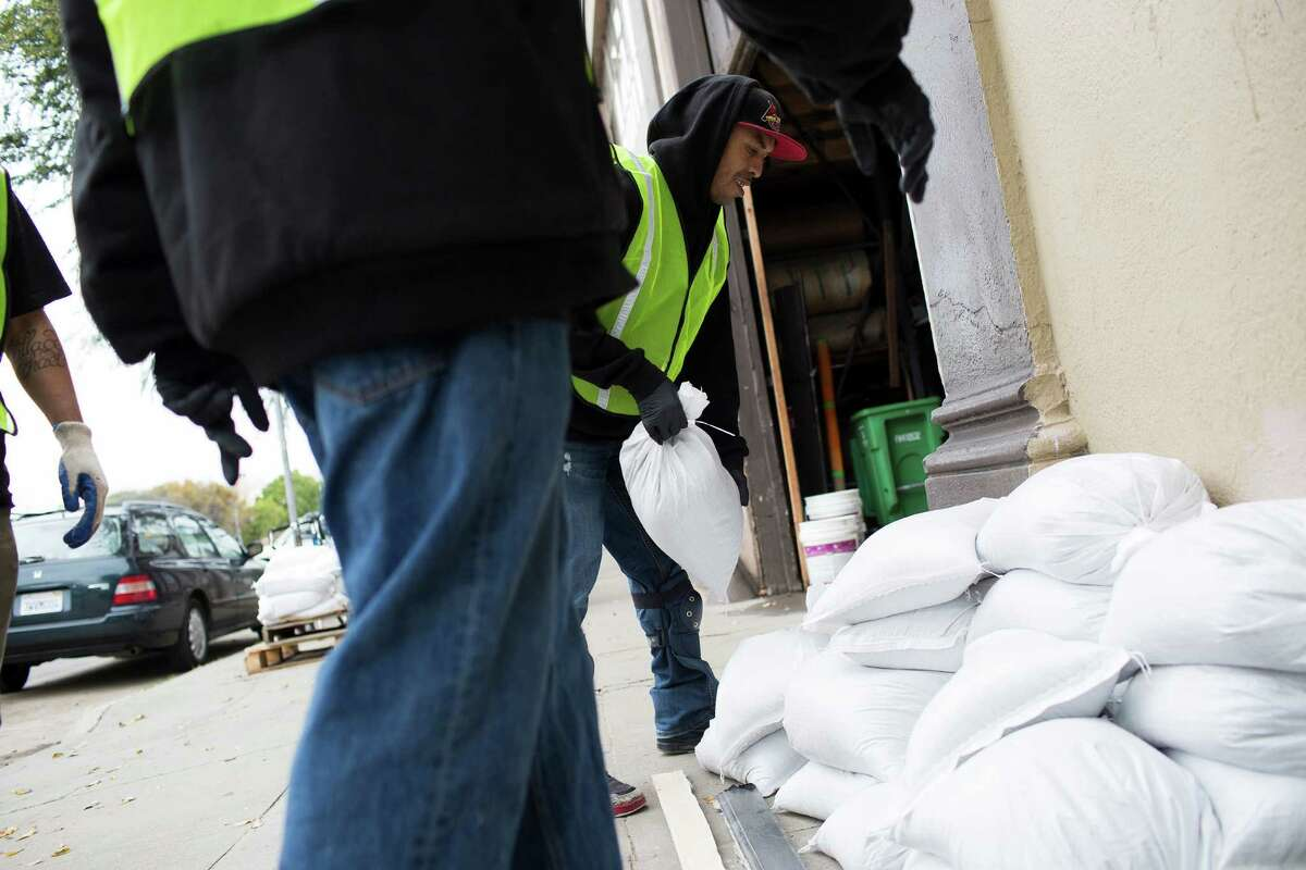 Workers with ServiceMasters Recovery Management sandbag residences at 17th St. and Folsom St. in preparation of a storm in San Francisco, Calif. on Wednesday, December 10, 2014. The properties in the area were damaged by floods in a relatively light storm last week.
