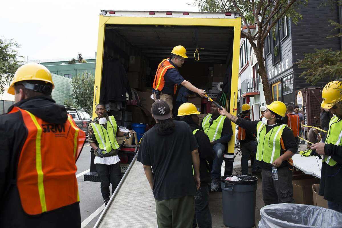 Workers with ServiceMasters Recovery Management prepare to sandbag residences at 17th St. and Folsom St. in preparation of a storm in San Francisco, Calif. on Wednesday, December 10, 2014. The properties in the area were damaged by floods in a relatively light storm last week.