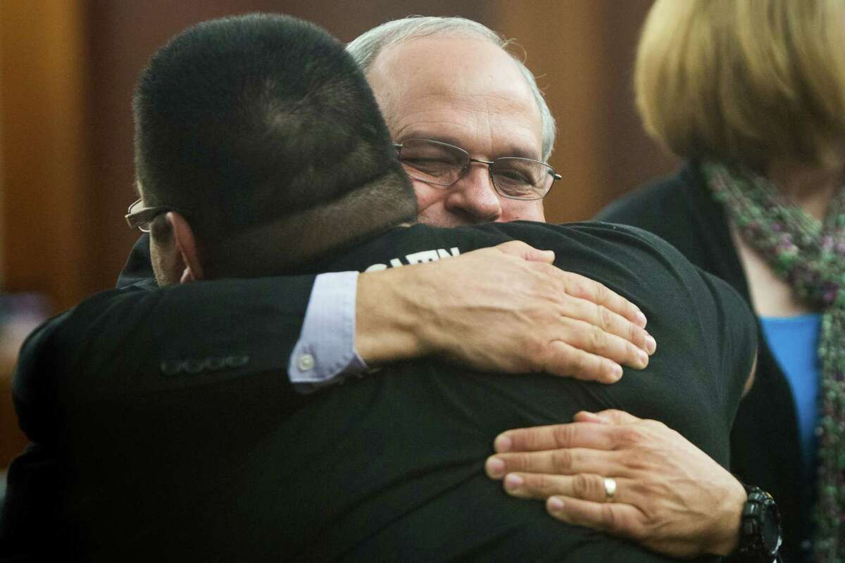 Randy Norman, the father of Chelsea Norman who was struck while riding her bicycle by Margaret Mayer, 35, hugs cyclist Ricardo Martinez after Mayer was found guilty by a jury of failing to stop to give aid to the victim. Wednesday, Dec. 10, 2014, in Houston.