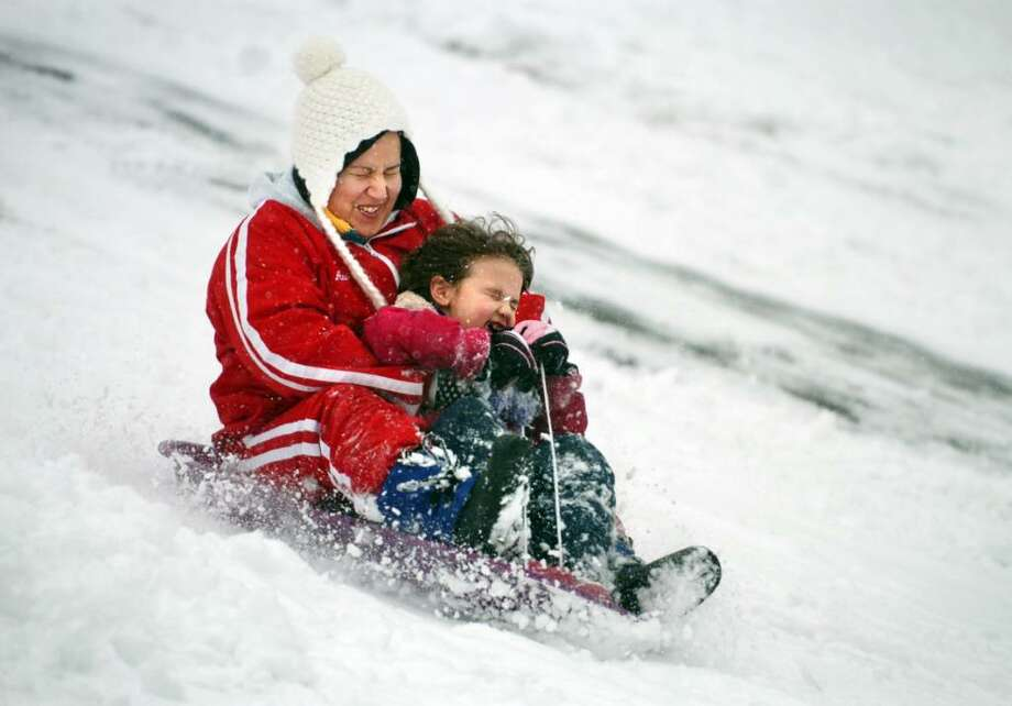 Seven-year-old Katie Flora, of Derby, and her babysitter Ana Diaz, 19, slide down the hill behind the new Derby Middle School Friday Feb. 26, 2010. Photo: Autumn Driscoll / Connecticut Post