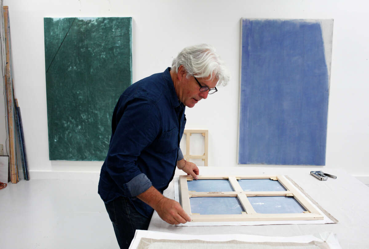 John Zurier mounts a painting on a canvas stretcher at his Oakland studio. His works are often monochromatic.
