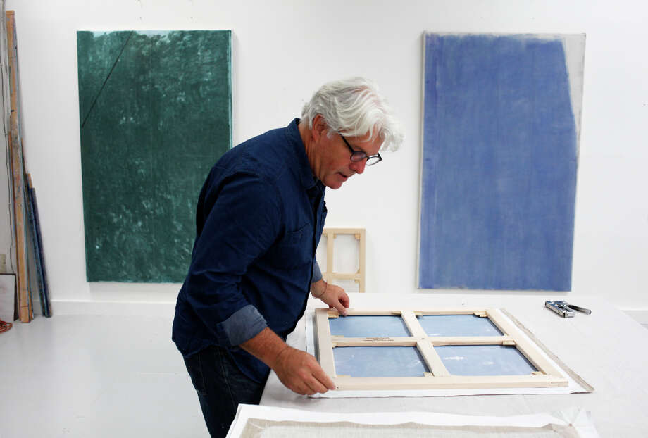 John Zurier mounts a painting on a canvas stretcher at his Oakland studio. His works are often monochromatic. Photo: Pete Kiehart / The Chronicle / ONLINE_YES