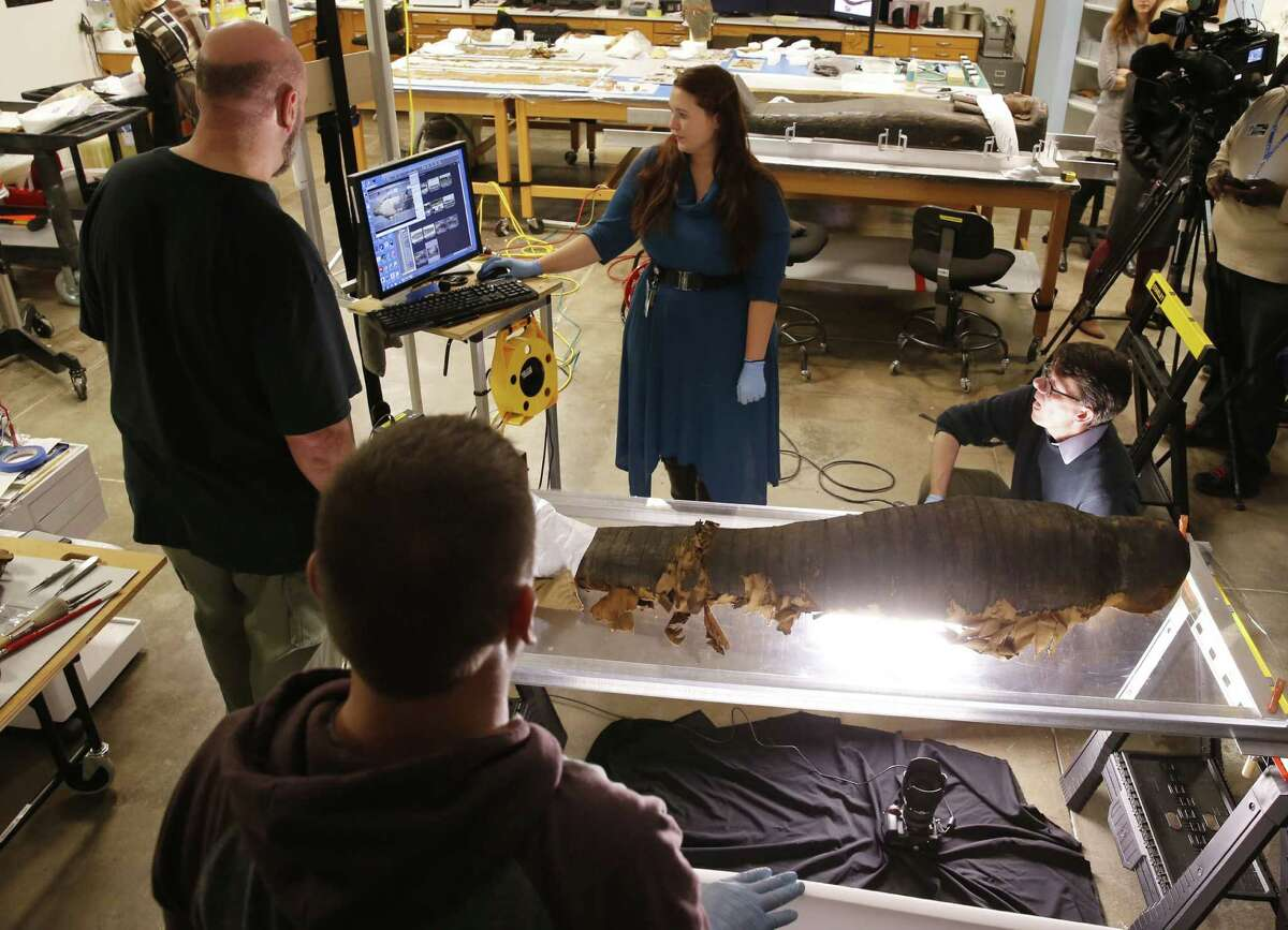 JP Brown, Regenstein Conservator at the Field Museum, right, and his team from left, Michael Marozas, Brian Cory, and Morgan Nau, photograph the backside of the mummified body of Minirdis, a 14-year-old Egyptian boy who was the son of a priest, Wednesday, Dec. 10, 2014, in Chicago. Brown, and his team opened the coffin of the 2,500-year-old mummy to perform conservation work before it becomes part of a traveling exhibition.