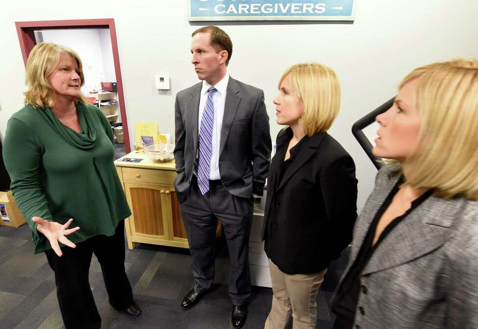 Kathy Burbank, executive director, left, of Community Caregivers meets with volunteers Ryan Murray, vice president, second from left, Bridget Murray, manager, second from right and Lauren Murray, manager of the Murray Group Insurance Services Monday morning Dec. 8, 2014 in Guilderland, N.Y. (Skip Dickstein/Times Union)