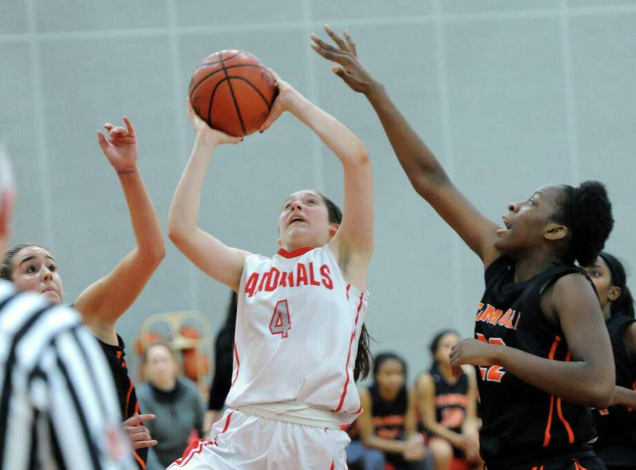 Leigh Galletta (#4) of Greenwich splits two Stamford defenders, including Oriana Merone (#22), right, to score during the girls high school basketball game between Greenwich High School and Stamford High School at Greenwich, Conn., Wednesday, Dec. 10, 2014. Photo: Bob Luckey / Greenwich Time