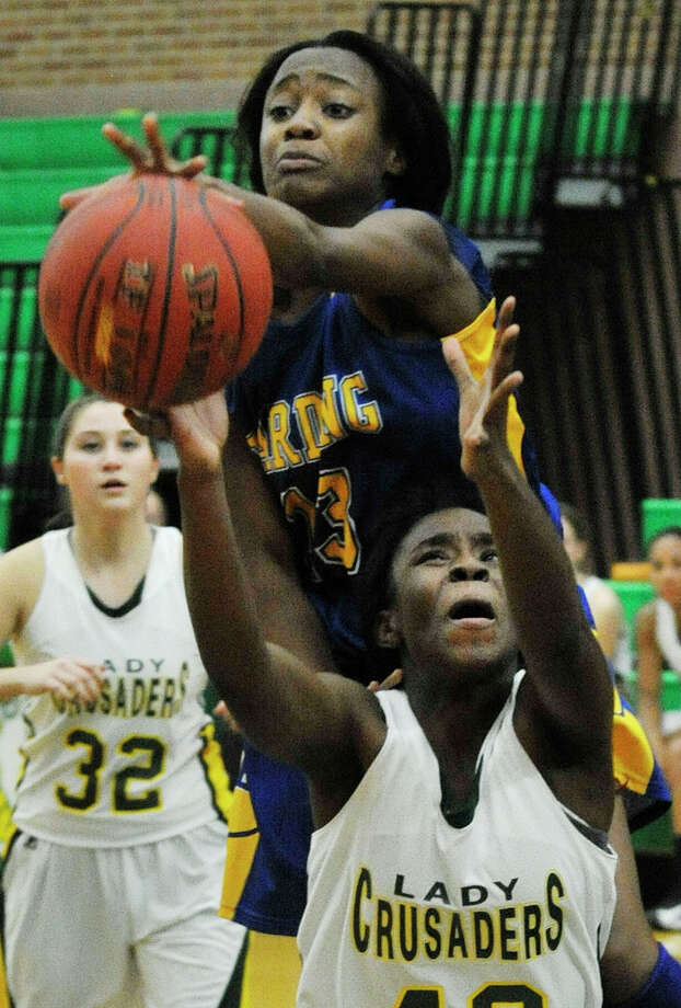 Harding's Sanice Davidson reaches over top of Trinity Catholic's Cheyenne Antoine during their basketball game at Trinity Catholic High School in Stamford, Conn., on Wednesday, Dec. 10, 2014. Trinity Catholic won, 57-41. Photo: Jason Rearick / Stamford Advocate