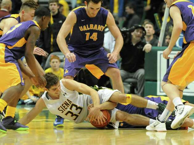 Siena's Rob Poole and UAlbany's Gary Johnson battle for the ball during a basketball game at the Times Union Center  Friday, Nov. 8, 2013 in Albany, N.Y. (Lori Van Buren / Times Union) Photo: Lori Van Buren / 00024543A