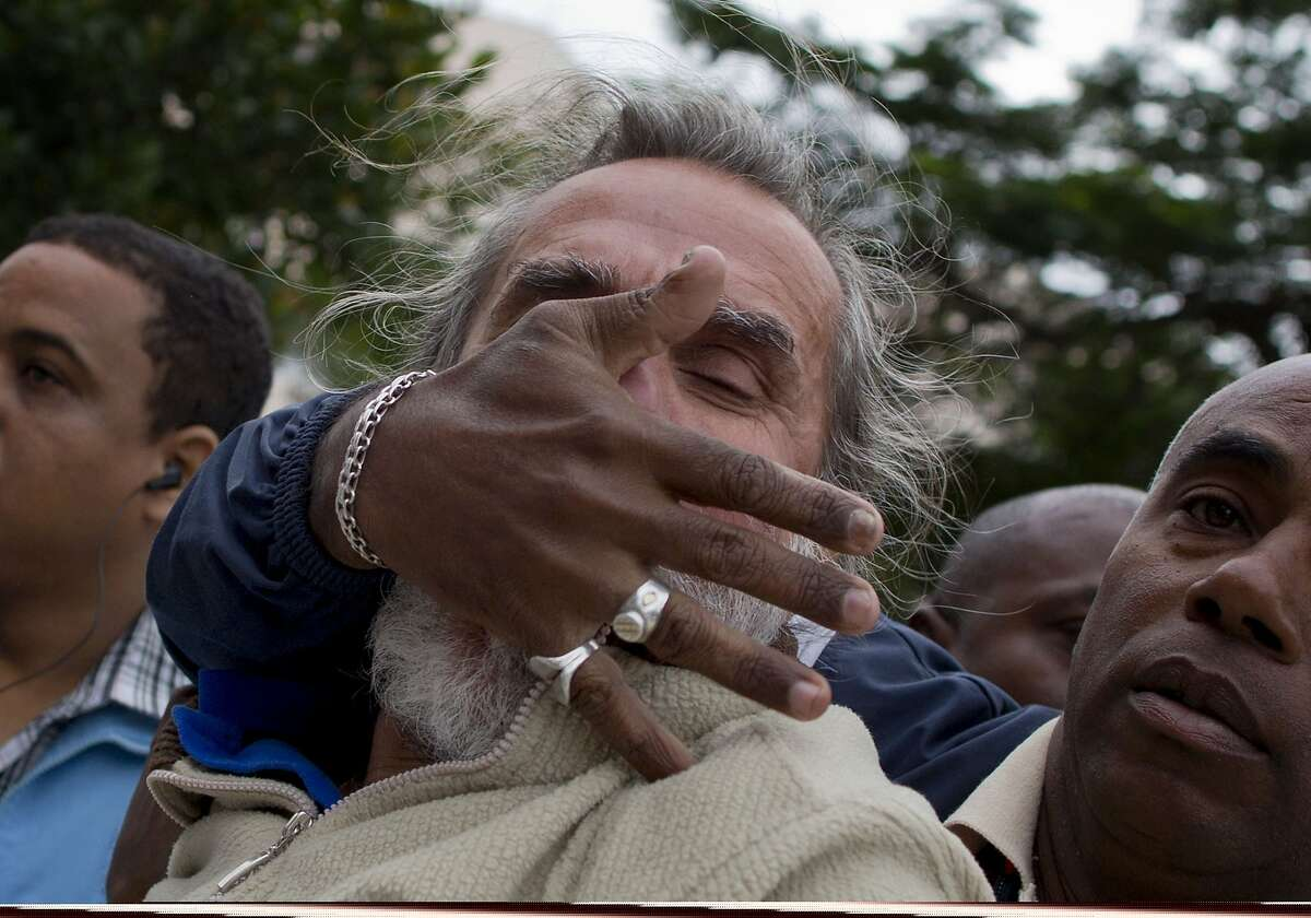 An opposition activist is detained by Cuban security officers before the start of a march marking International Human Rights Day in Havana, Cuba, Wednesday, Dec. 10, 2014. The march was organized by the
