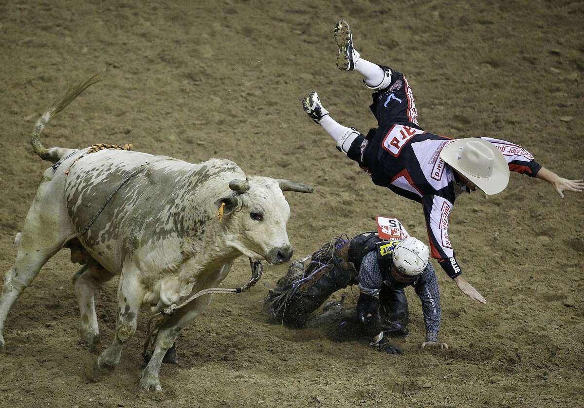 Bullfighter Chuck Swisher, top, gets tossed into the air by bull Cajun Smurf while Swisher was protecting Bull rider Trey Benton III during the seventh go-round of the National Finals Rodeo, Wednesday, Dec. 10, 2014, in Las Vegas. (AP Photo/John Locher)
