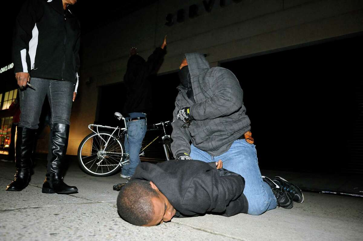 An undercover officer detains a protester who allegedly struck the officer a confrontation in Oakland on Dec. 10.