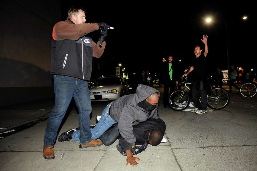 An under cover officer points his gun at the crowd while his partner subdues a protester who struck him in the back of the head, as demonstrations continue for a fifth night in Oakland on Wednesday, Dec. 10, 2014.