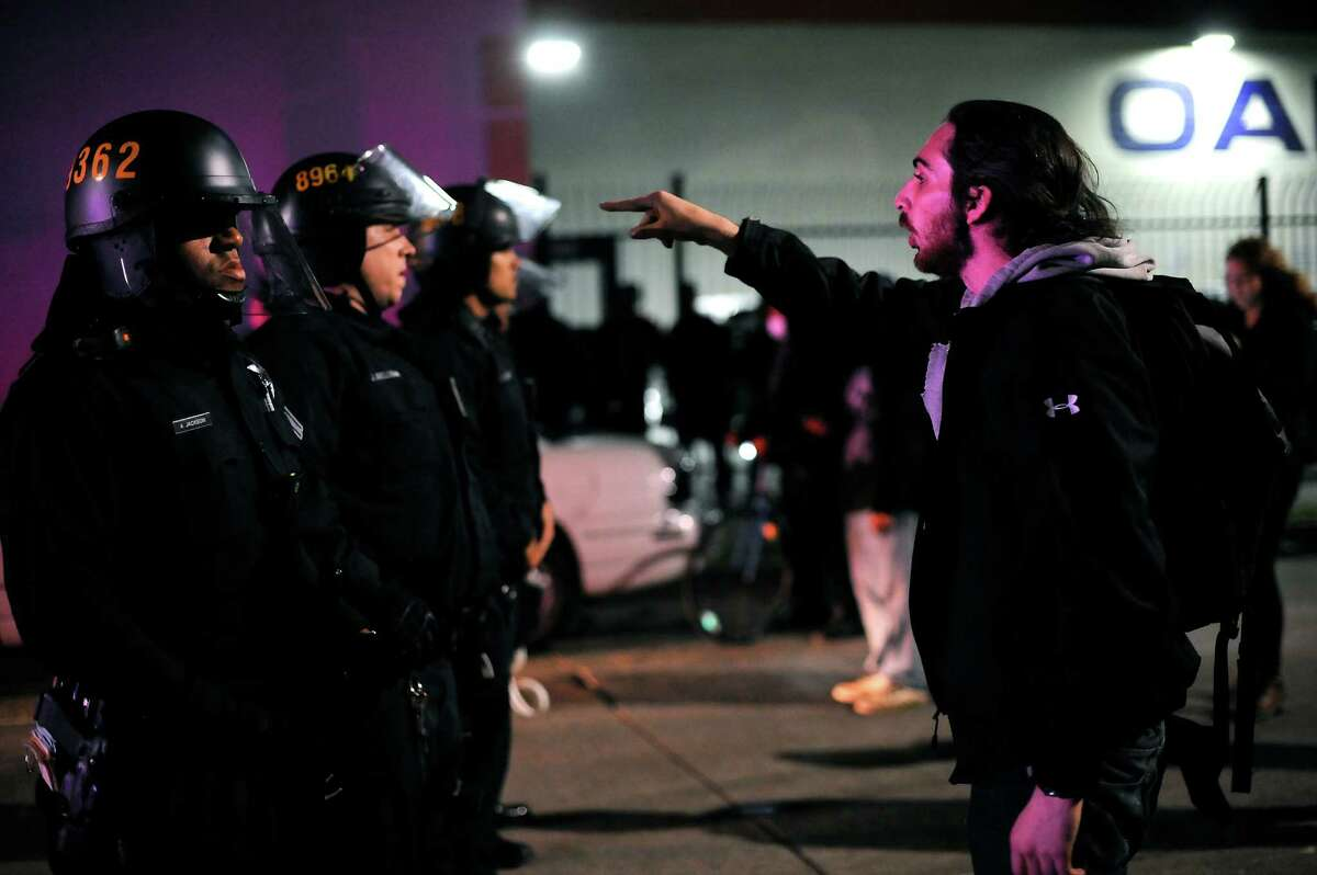 A protester during a recent demonstration in Oakland yells at police officers holding the line after undercover officers detained another protester and pushed the crowd back.
