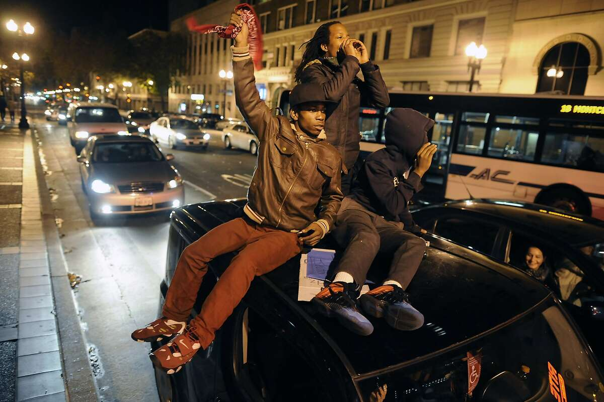 People ride on top of a car as marchers make their way down Telegraph Ave. during the fifth night of protests in Oakland, CA, on Wednesday, December 10, 2014.