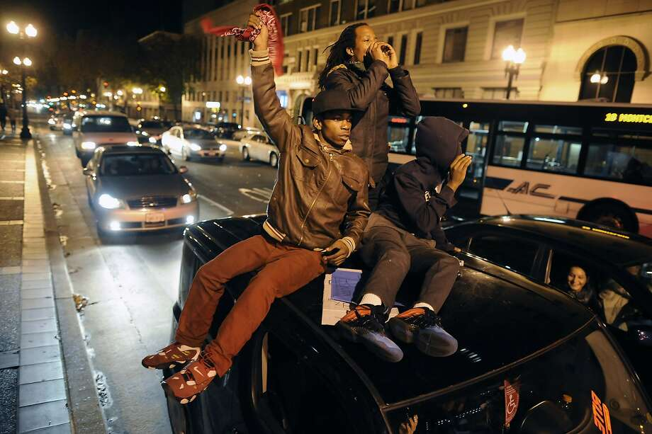 People ride on top of a car as marchers make their way down Telegraph Ave. during the fifth night of protests in Oakland, CA, on Wednesday, December 10, 2014. Photo: Michael Short, Special To The Chronicle
