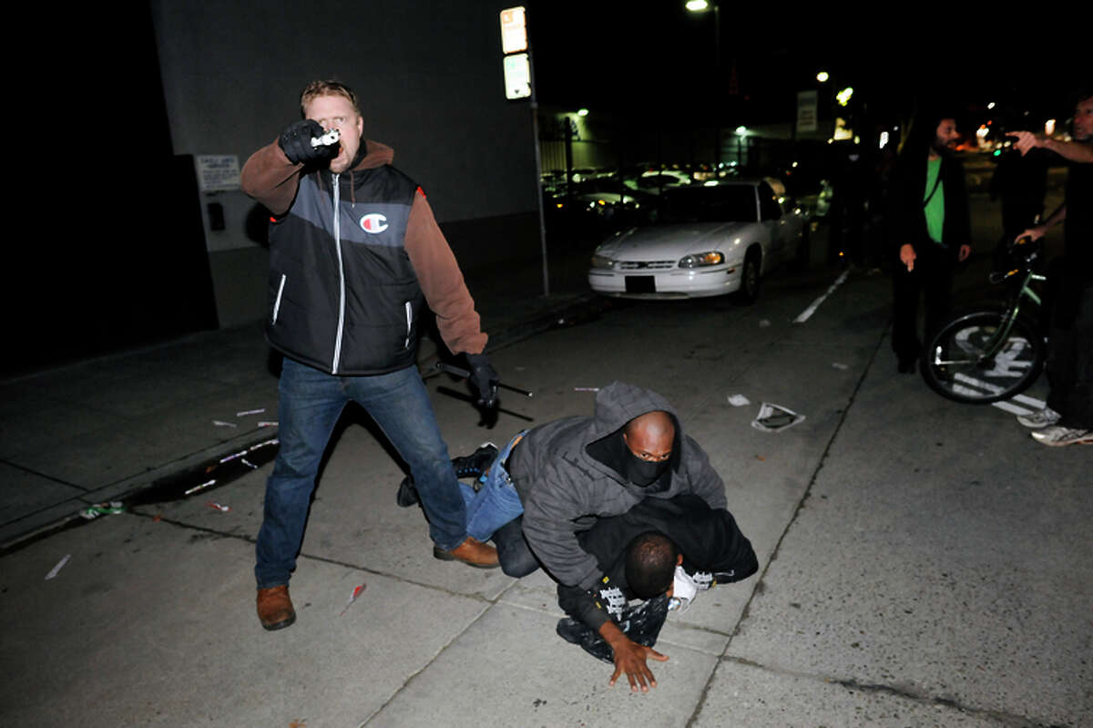 A plainclothes CHP officer points his gun at the crowd while his partner subdues a protester who struck him in the back of the head in Oakland on Dec. 10, 2014.
