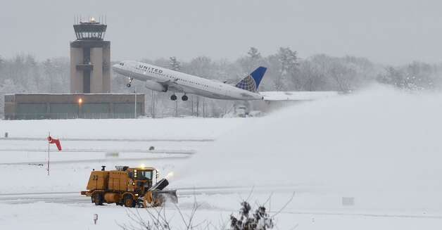 As a plane takes off in the background, a high-powered snowblower keeps the taxiway clear for other planes at Albany International Airport on Thursday, Dec. 11, 2014. (Skip Dickstein / Times Union)