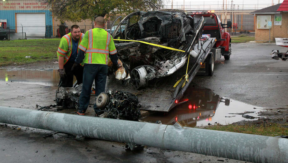 A wrecker crew cleans up by a burned vehicle that slammed into a pole about 3:30 a.m. Thursday December 11, 2014 at FM 78 and Ackerman in Kirby. The driver of the vehicle died at the scene. Photo: JOHN DAVENPORT, San Antonio Express-News / ©San Antonio Express-News/John Davenport