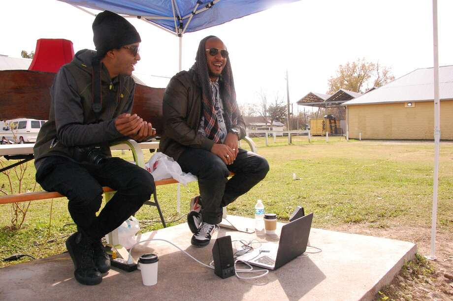 The Black Guys, Robert Hodge and Phillip Pyle II, sit by the bus stop near their studio in the Third Ward.
