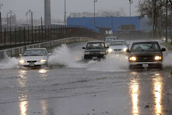 Cars navigate through standing water at the corner of E. 8th ave. and 10th street in Oakland, Calif., on Thursday Dec. 11, 2014, as a heavy rainstorm begins to move across the Bay Area.