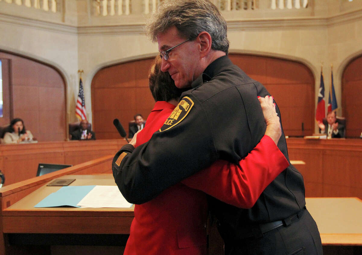Retiring San Antonio Police Chief William McManus, left, gets a is hug from City Manager Sheryl Sculley during a meeting of the San Antonio City Council, Thursday, Dec. 11, 2014. The chief has been with the department since March of 2006. McManus is retiring from law enforcement after 40 years and will head the security operations at CPS Energy.