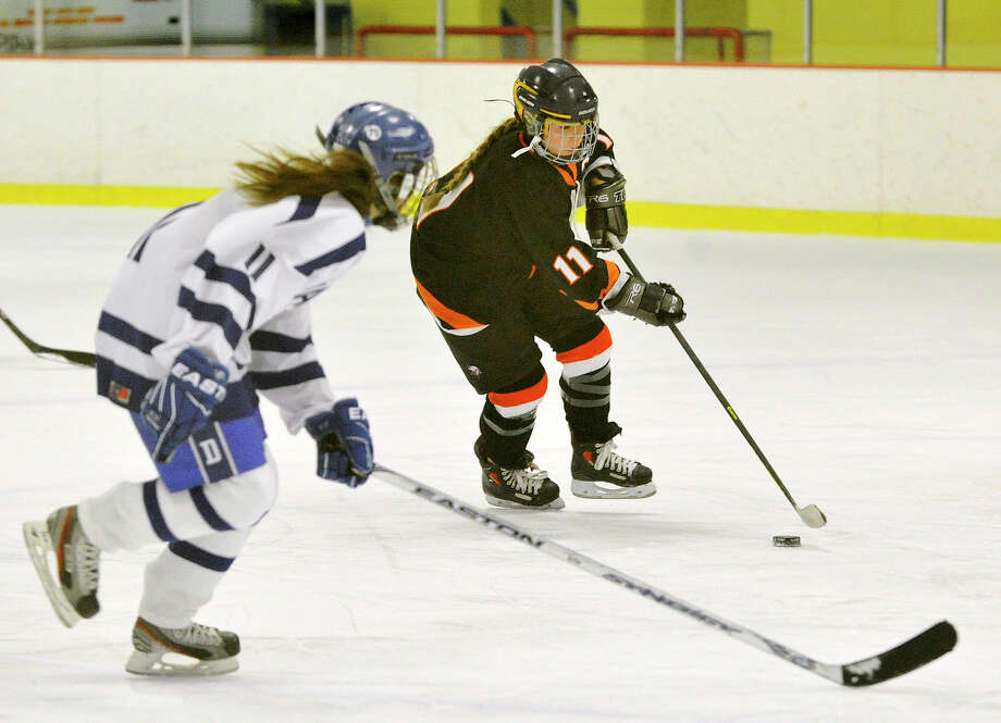 Stamford/Westhill/Staples' Cassandra Miolene brings the puck up the ice meeting Darien's Lauren Cicero during their hockey game at Terry Conners Rink in Stamford, Conn., on Monday, Jan. 13, 2014. Darien won, 7-0. Photo: Jason Rearick / Stamford Advocate