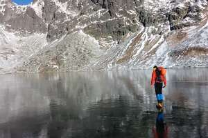 Hikers walk across crystal clear frozen lake in Slovakia - Photo