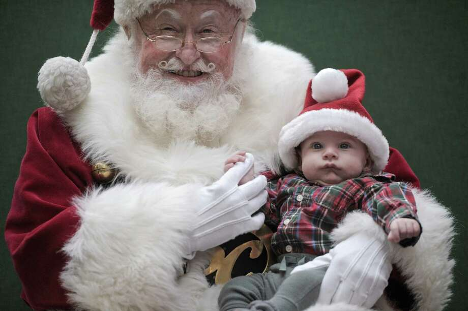 Miles Silvera, 3 months, from New York, New York, holds on to Santa's finger while having his first photo with Santa taken at the Danbury Fair Mall, on Thursday, December 11, 2014, in Danbury, Conn. Miles was in Danbury visiting his grandmother. Santa is James Herbermann, 69, of Santa Rosa Beach, Florida. Photo: H John Voorhees III / The News-Times