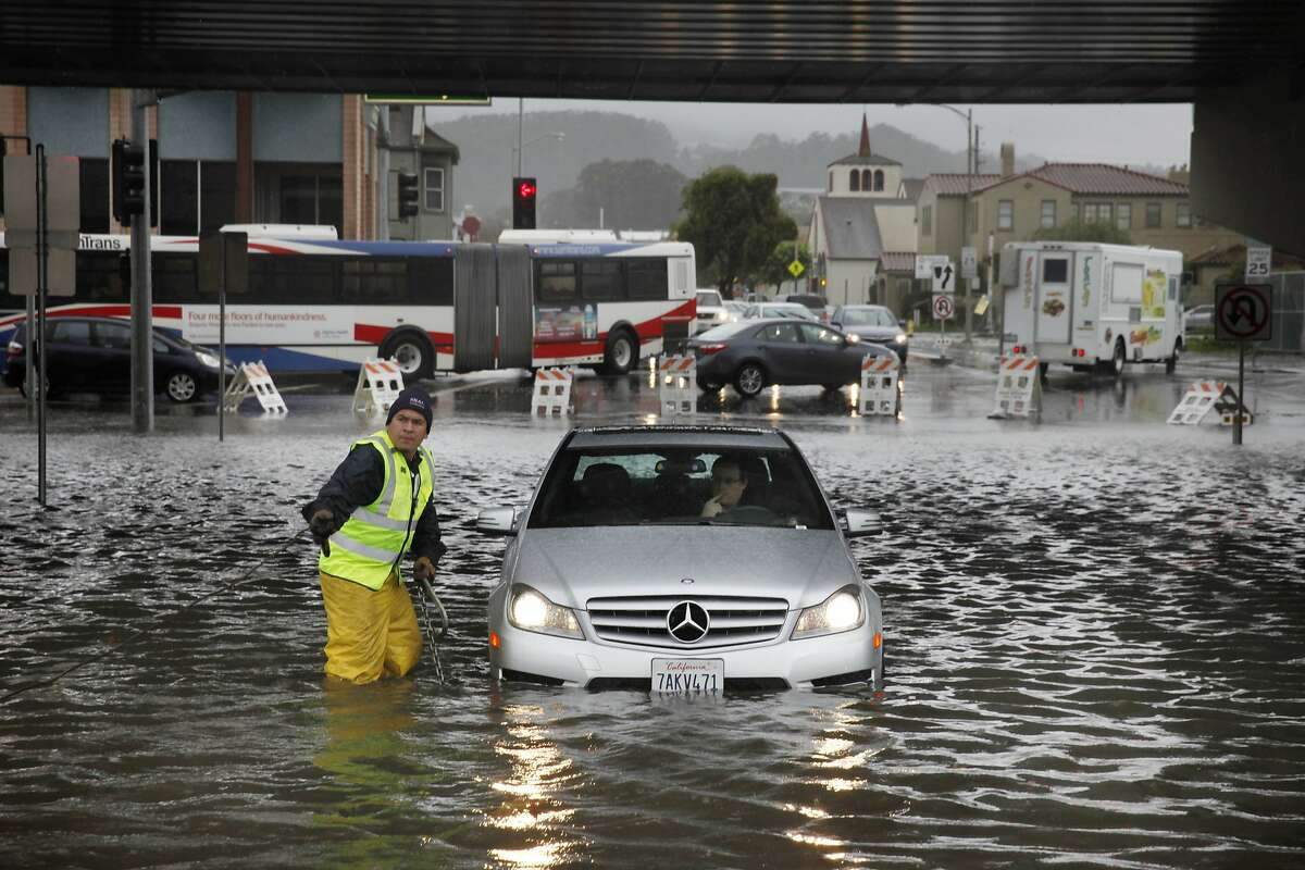 Armando Carlin (l to r), tow truck driver, prepares to tow the rental car of Paul Latimer (in car) of Austin, Texas after it stopped in standing water while driving on San Bruno Avenue between Huntington Avenue and San Mateo Avenue on his way to the airport on Thursday, December 11, 2014 in San Bruno, Calif. That section of roadway was closed to traffic by barriers.