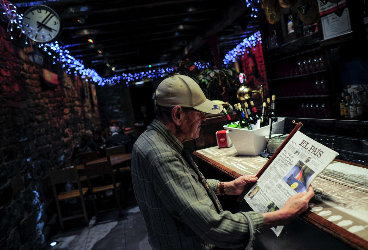 A man reads El Pais, a leading newspaper in Spain, at a bar in Pamplona on the day Google announced it would shut down its News site ahead of the effective date of the country's law that will require aggregators to pay to link content.