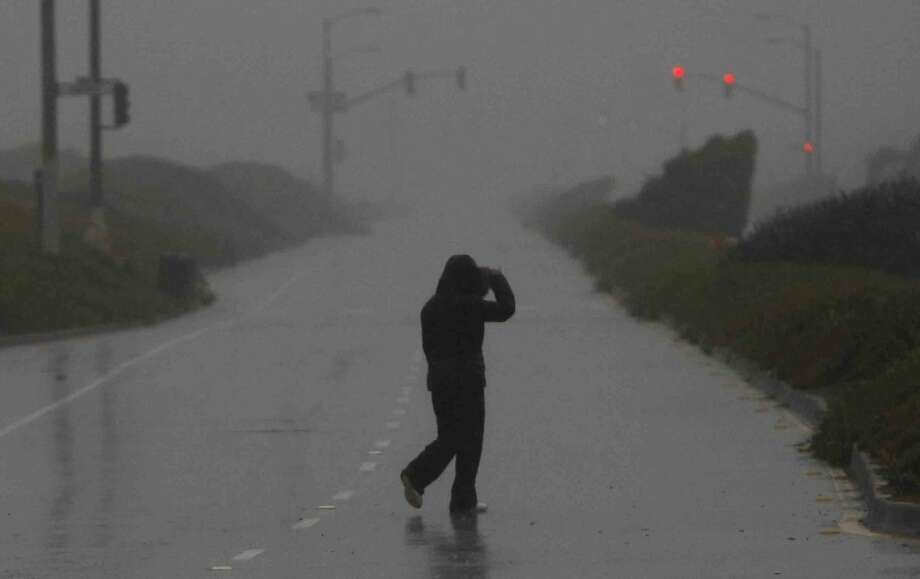 FILE PHOTO: A person walks across Great Highway which was closed due to risk of high flooding and strong winds near Ocean Beach in San Francisco, Calif. Thursday, December 11, 2014 during the biggest storm to hit the Bay Area in 6 years Photo: Jessica Christian, The Chronicle