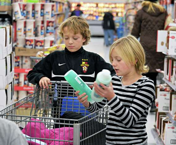 Jackson Mateja, 11, left, and his sister  Madeleine Mateja, 9, of Loudonville pick out shampoos as their family shops  at Wal-mart in Crossgates Commons for supplies to be delivered to the Equinox shelter on Christmas Eve day as part of the Morning of Kindness program  Thursday Dec. 4, 2014, in Albany, NY.  (John Carl D'Annibale / Times Union) Photo: John Carl D'Annibale / 00029737A