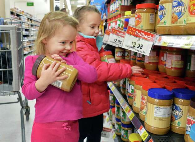 Three-year-old twins Abby, left, and Emme Fazziola of Loudonville, load up on peanut butter as the help their mother shop at Wal-mart in Crossgates Commons for food to be delivered to the city mission on Christmas Eve day as part of the Morning of Kindness program  Thursday Dec. 4, 2014, in Albany, NY.  (John Carl D'Annibale / Times Union) Photo: John Carl D'Annibale / 00029737A