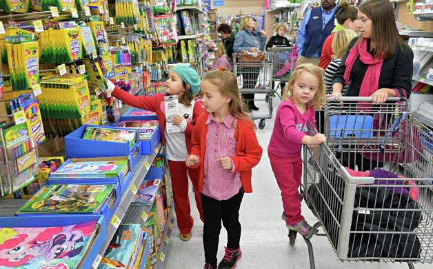 Justine Fazziola, right, her children and friends, all of Loudonville, shop at at Wal-mart in Crossgates Commons for supplies to be delivered to charities on Christmas Eve day as part of the Morning of Kindness program  Thursday Dec. 4, 2014, in Albany, NY.  (John Carl D'Annibale / Times Union) Photo: John Carl D'Annibale / 00029737A