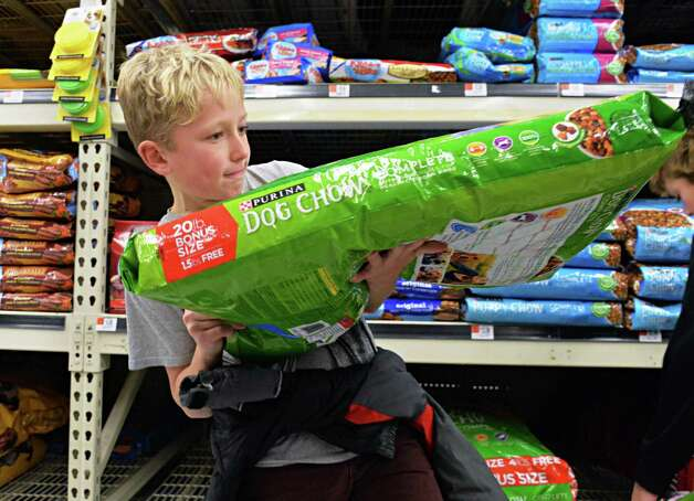 Nine-year-old Braeden Mateja of Loudonville hefts a bag of dog food as his family shops at at Wal-mart in Crossgates Commons for pet supplies to be delivered to the humane society on Christmas Eve day as part of the Morning of Kindness program  Thursday Dec. 4, 2014, in Albany, NY.  (John Carl D'Annibale / Times Union) Photo: John Carl D'Annibale / 00029737A