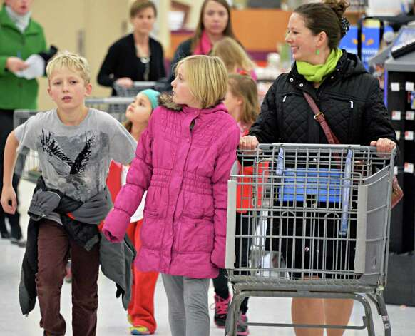 Kelly Mateja, right, her children and friends, all of Loudonville, shop at at Wal-mart in Crossgates Commons for supplies to be delivered to charities on Christmas Eve day as part of the Morning of Kindness program  Thursday Dec. 4, 2014, in Albany, NY.  (John Carl D'Annibale / Times Union) Photo: John Carl D'Annibale / 00029737A