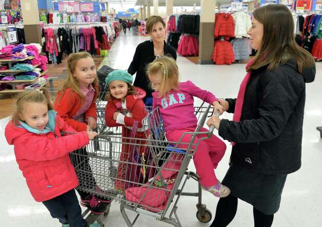 Kristen Diesel, center, and Justine Fazziola and their families, all of Loudonville, shop at at Wal-mart in Crossgates Commons for supplies to be delivered to charities on Christmas Eve day as part of the Morning of Kindness program  Thursday Dec. 4, 2014, in Albany, NY.  (John Carl D'Annibale / Times Union) Photo: John Carl D'Annibale / 00029737A