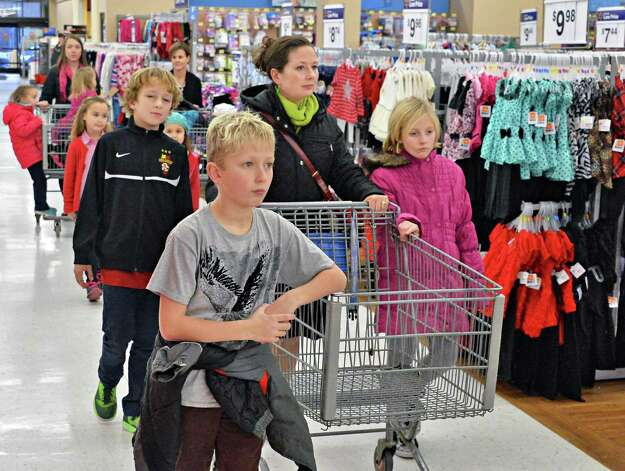 Kelly Mateja, center, her children and friends, all of Loudonville, shop at at Wal-mart in Crossgates Commons for supplies to be delivered to charities on Christmas Eve day as part of the Morning of Kindness program  Thursday Dec. 4, 2014, in Albany, NY.  (John Carl D'Annibale / Times Union) Photo: John Carl D'Annibale / 00029737A