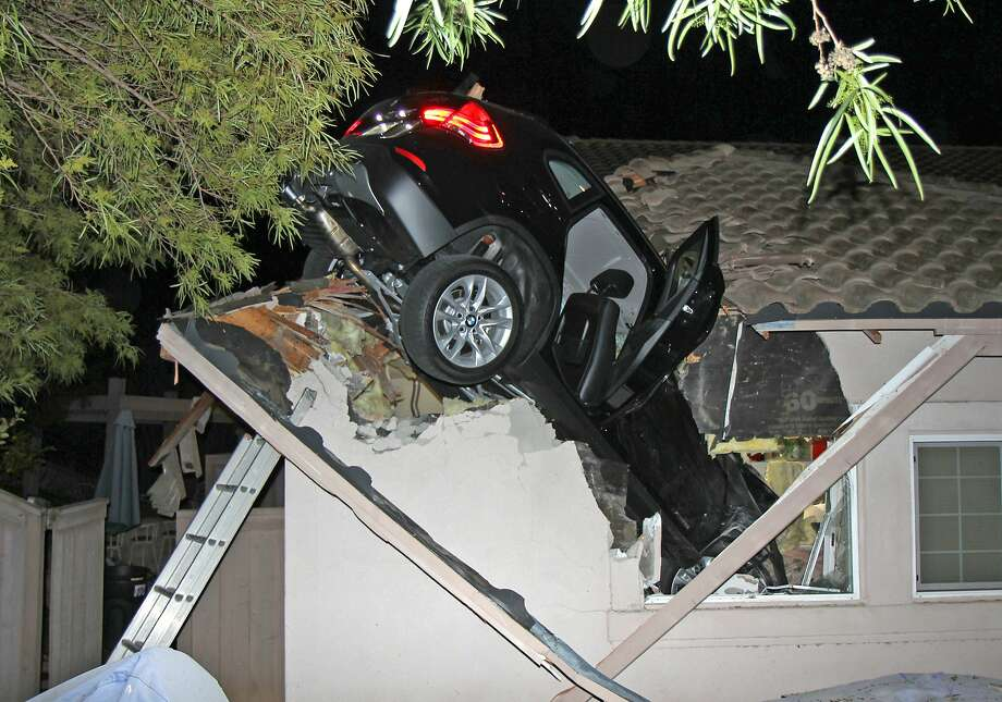 SORRY TO DROP IN ON YOU LIKE THIS:George Strother and his wife were at home in Escondido, Calif., when a BMW SUV lost control on a turn and sailed off a roadway above their house. The BMW plunged 20 feet and crashed through their garage roof, landing on the hood of Strother's Nissan Pathfinder. Strother and his wife were not injured and, amazingly enough, neither was the driver of the BMW. Photo: George Strother, Associated Press