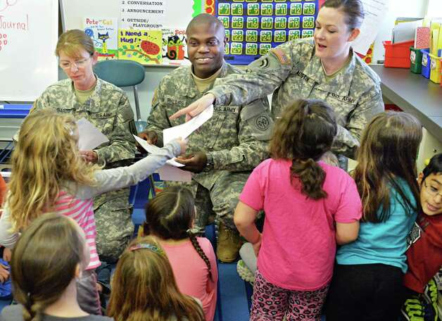New York Army National Guard soldiers, from left, M Sgt. Corine Lombardo, Maj. Al Phillips and S Sgt. Patricia Austin receive holiday thank you cards from Jennie Bauer's first grader class at Latham Ridge Elementary School Thursday Dec. 11, 2014, in Colonie, NY.   (John Carl D'Annibale / Times Union) Photo: John Carl D'Annibale / 00029796A