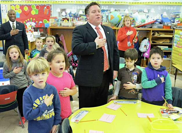 Albany County Executive Daniel McCoy, center, leads students in Jennie Bauer's first grader class at Latham Ridge Elementary School in the Pledge of Allegiance before a ceremony to present holiday thank you cards from the class to veterans Thursday Dec. 11, 2014, in Colonie, NY.   (John Carl D'Annibale / Times Union) Photo: John Carl D'Annibale / 00029796A