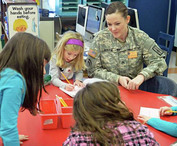 New York Army National Guard  S Sgt. Patricia Austin with students in Jennie Bauer's first grader class at Latham Ridge Elementary School before a ceremony to present holiday thank you cards from the class to veterans Thursday Dec. 11, 2014, in Colonie, NY.   (John Carl D'Annibale / Times Union) Photo: John Carl D'Annibale / 00029796A