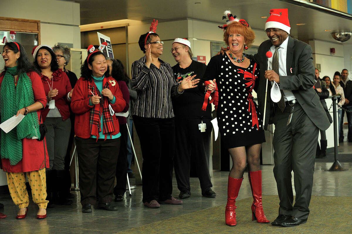 Sammy Alemseghed, right, dandces with Esther Librandi as carolers sing during the annual tree lighting ceremony at the Stamford Government Center in Stamford, Conn., on Thursday, Dec. 11, 2014.