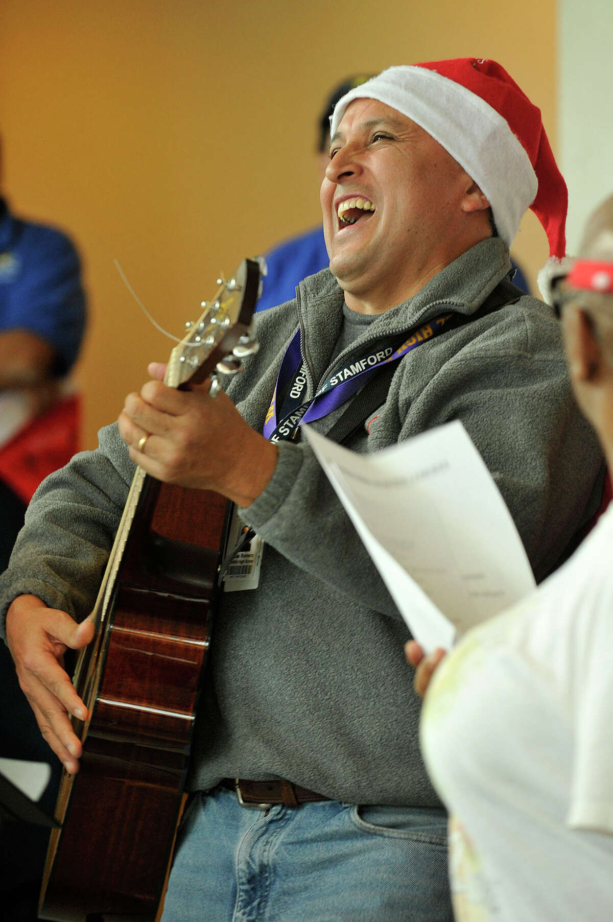 Lucas Romero leads the carolers by playing a guitar during the annual tree lighting ceremony at the Stamford Government Center in Stamford, Conn., on Thursday, Dec. 11, 2014.