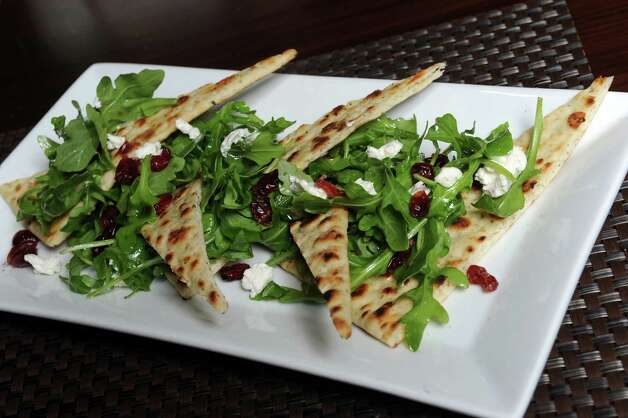 featured flat bread with crispy grilled crust, cranberry, goat cheese and arugula salad at Charter restaurant at Hilton on Tuesday Dec. 9, 2014 in Albany, N.Y.  (Michael P. Farrell/Times Union) Photo: Michael P. Farrell / 00029692A