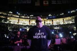 """Los Angeles Lakers' Carlos Boozer stands before team introductions for an NBA basketball game against the Sacramento Kings, Tuesday, Dec. 9, 2014, in Los Angeles. Several athletes have worn """"I Can't Breathe"""" shirtsin support of the family of Eric Garner, who died July 17 after a police officer placed him in a chokehold when he was being arrested for selling loose, untaxed cigarettes. (AP Photo/Jae C. Hong)"""