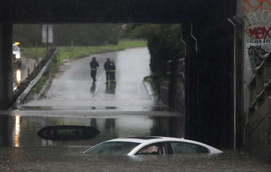 Berkeley firefighters stand on the on-ramp to eastbound I-80 beyond cars partially submerged in a flooded section of the Ashby Avenue underpass as a major storm hits the area in Berkeley, Calif. on Thursday, Dec. 11, 2014. Photo: Paul Chinn, The Chronicle